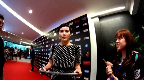 ZOE TAY wears a short bob and a black short-sleeved Gucci dress